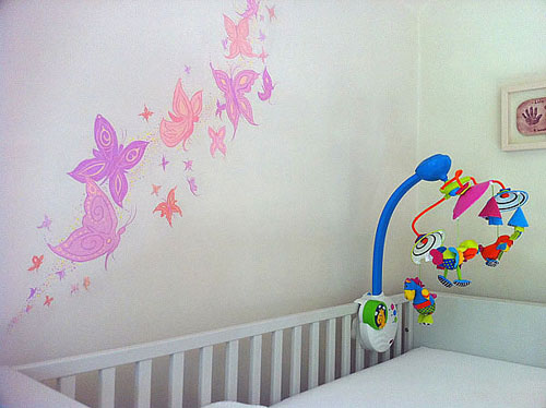 drugeliai ant sienos virš kūdikio lovytės