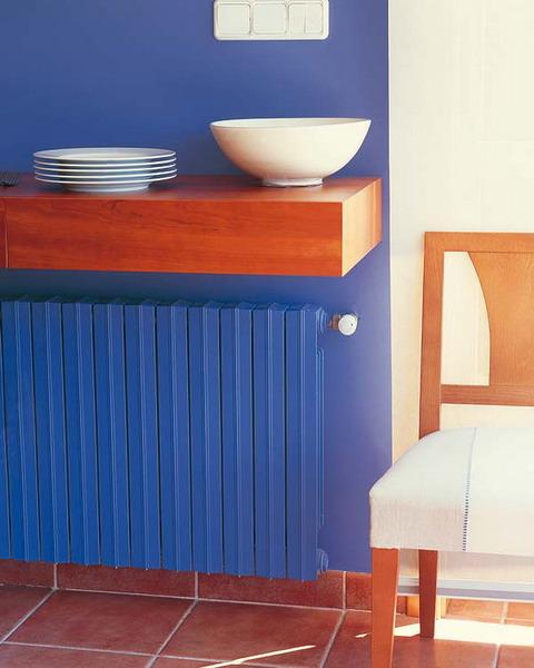 mėlynos spalvos dažais dažytas radiatorius ir siena
