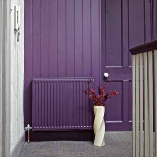 violetinės spalvos dažais dažytas radiatorius ir siena
