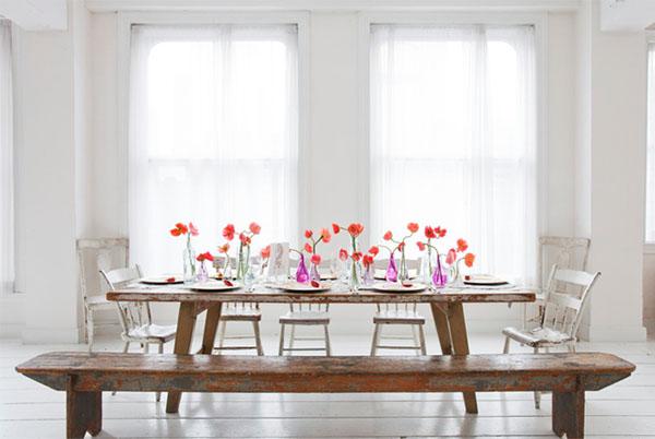 Raudonomis gėlėmis papuoštas stalas