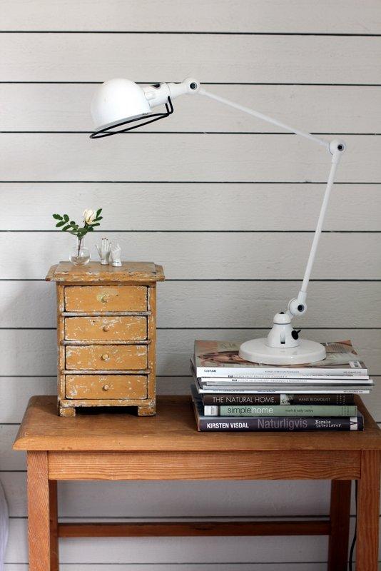 sena spintelė ant stalo, šviestuvas, knygos
