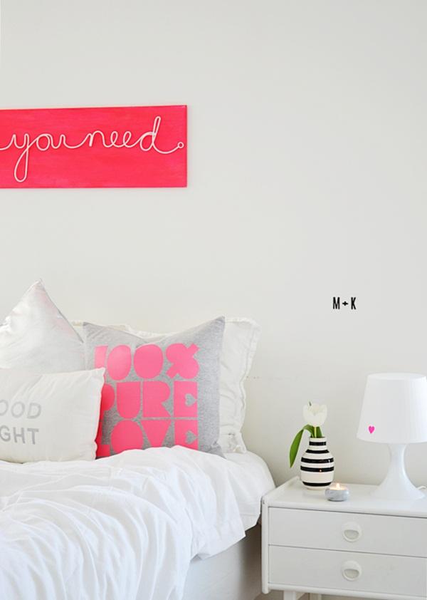 rausva lentelė ir balta pagalvė su užrašais miegamąjame