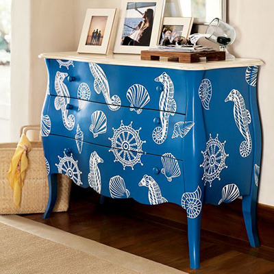 mėlyna komoda dekoruota baltais piešiniais