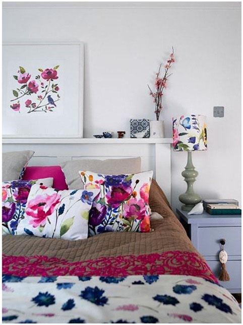 violetinių gėlių motyvai paveiksle, šviestuvo gaubte, pagalvėlėse ant lovos