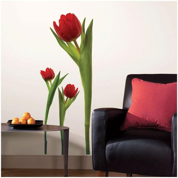 trys didelės tulpės ant sienos šalia juodo fotelio