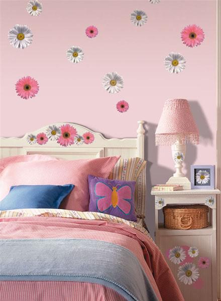 gėlių žiedai ant sienos, lovos atlošo, spintelės vaiko kambaryje