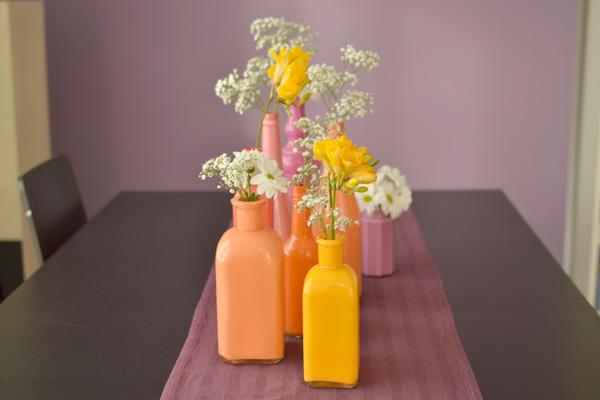 dažyti buteliai, vazelės ant stalo