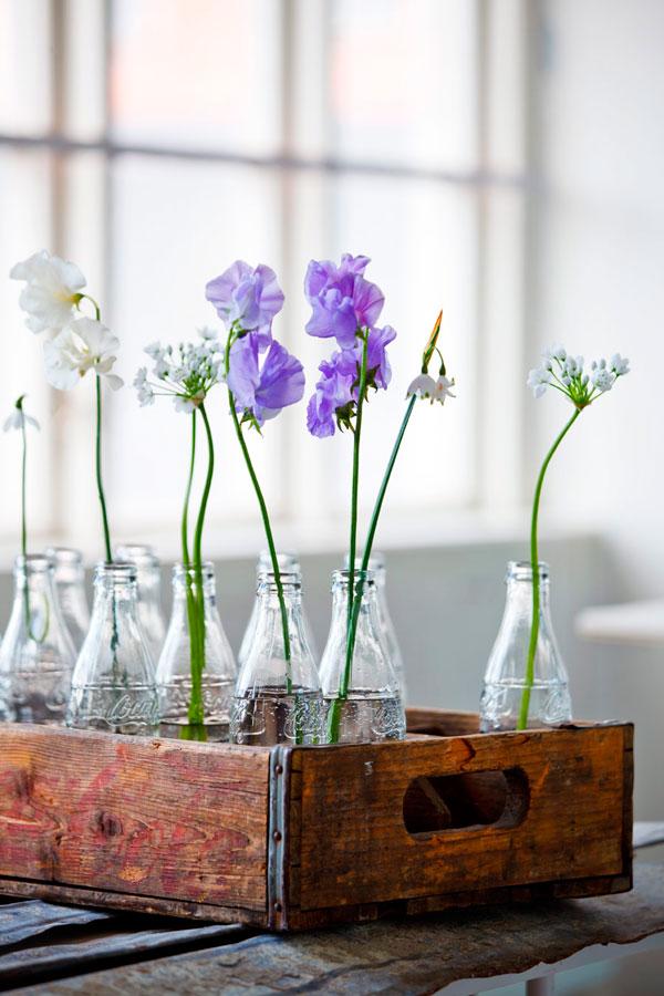 Gėlės permatomo stiklo vazelėse ir buteliukuose