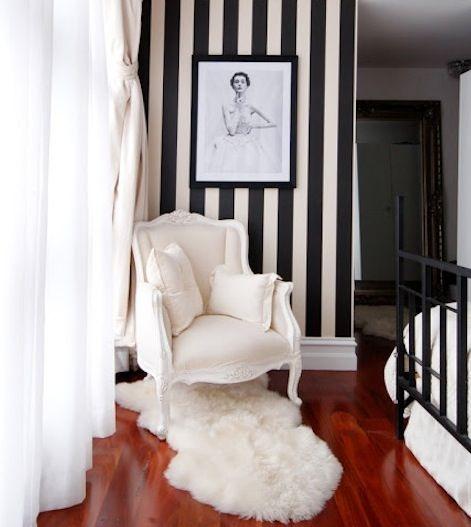 baltas fotelis juoda balta vertikaliai juostuota siena